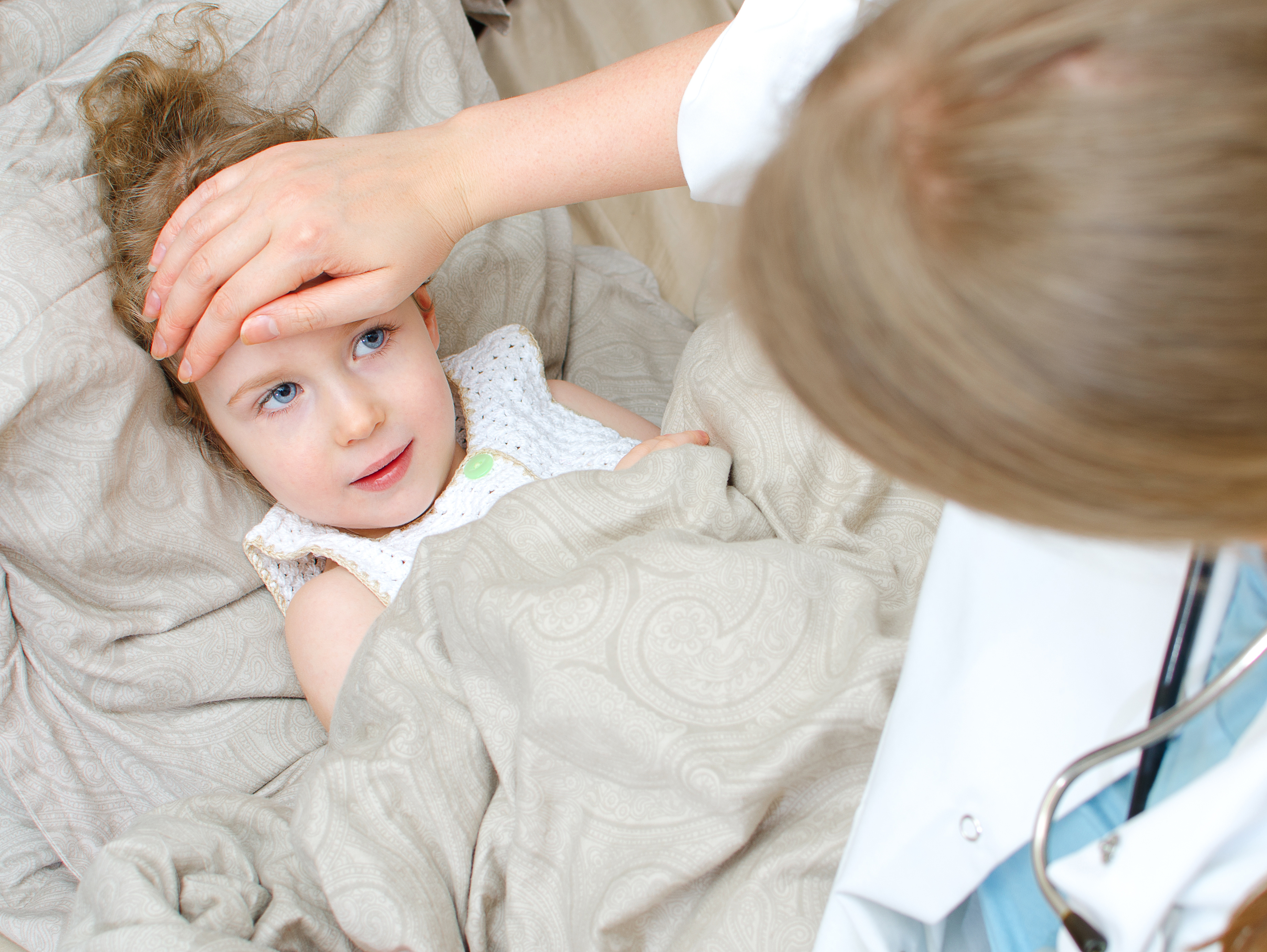 Top view of sick child lying in bed and visiting her doctor