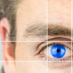 Young man with a vivid blue eye with parallel lines drawing your attention in a conceptual image of mental perception, visionary, intelligence or optics and eyesight.