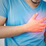 Man is clutching her chest, acute pain possible heart attack