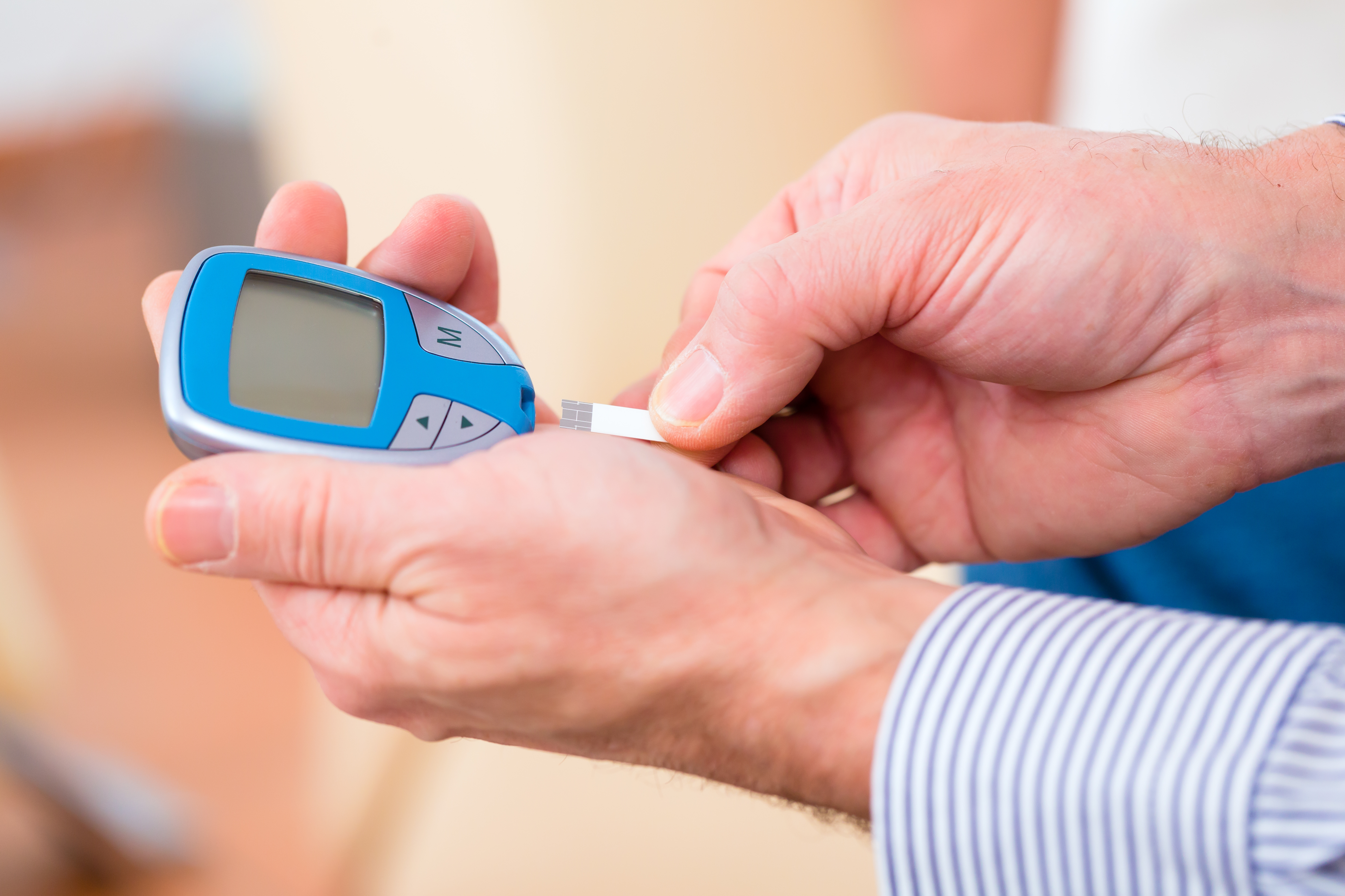 Man with adult onset diabetes measuring blood sugar with indicator