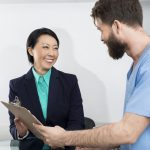 Happy receptionist and doctor discussing over clipboard in hospital