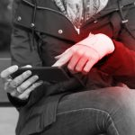 Woman with a injured wrist wrapped in an bandage, using a smartphone feeling pain, outdoors. Black and white image, pain area of red color.