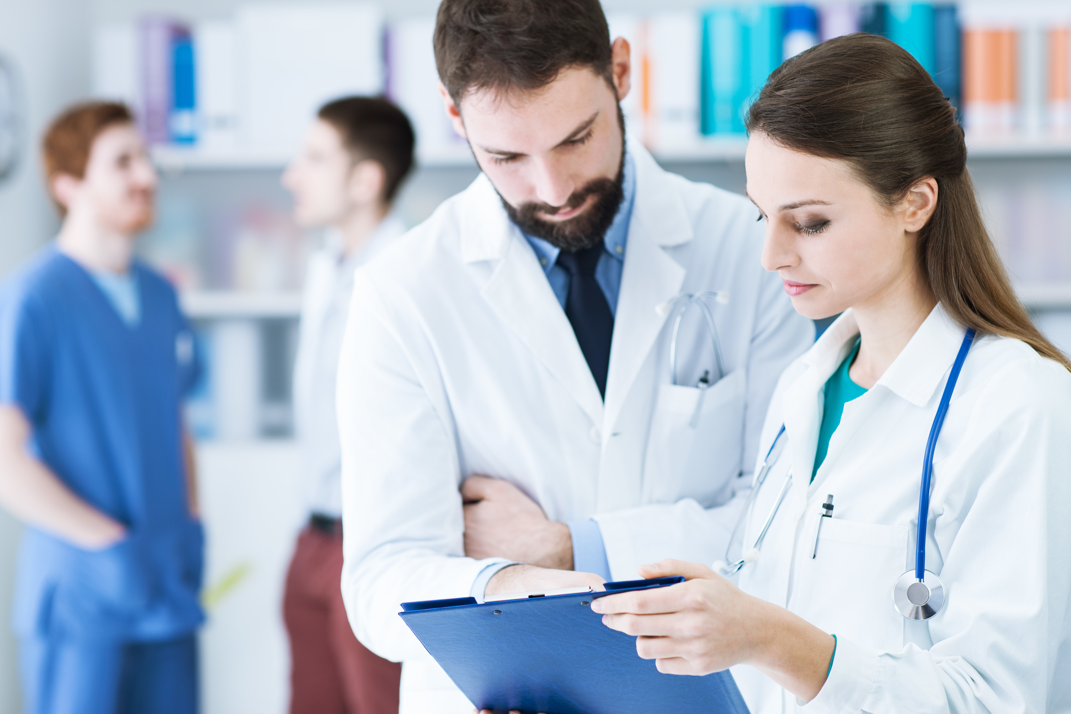 Doctors in the office checking patient's medical records on a clipboard, teamwork and healthcare concept