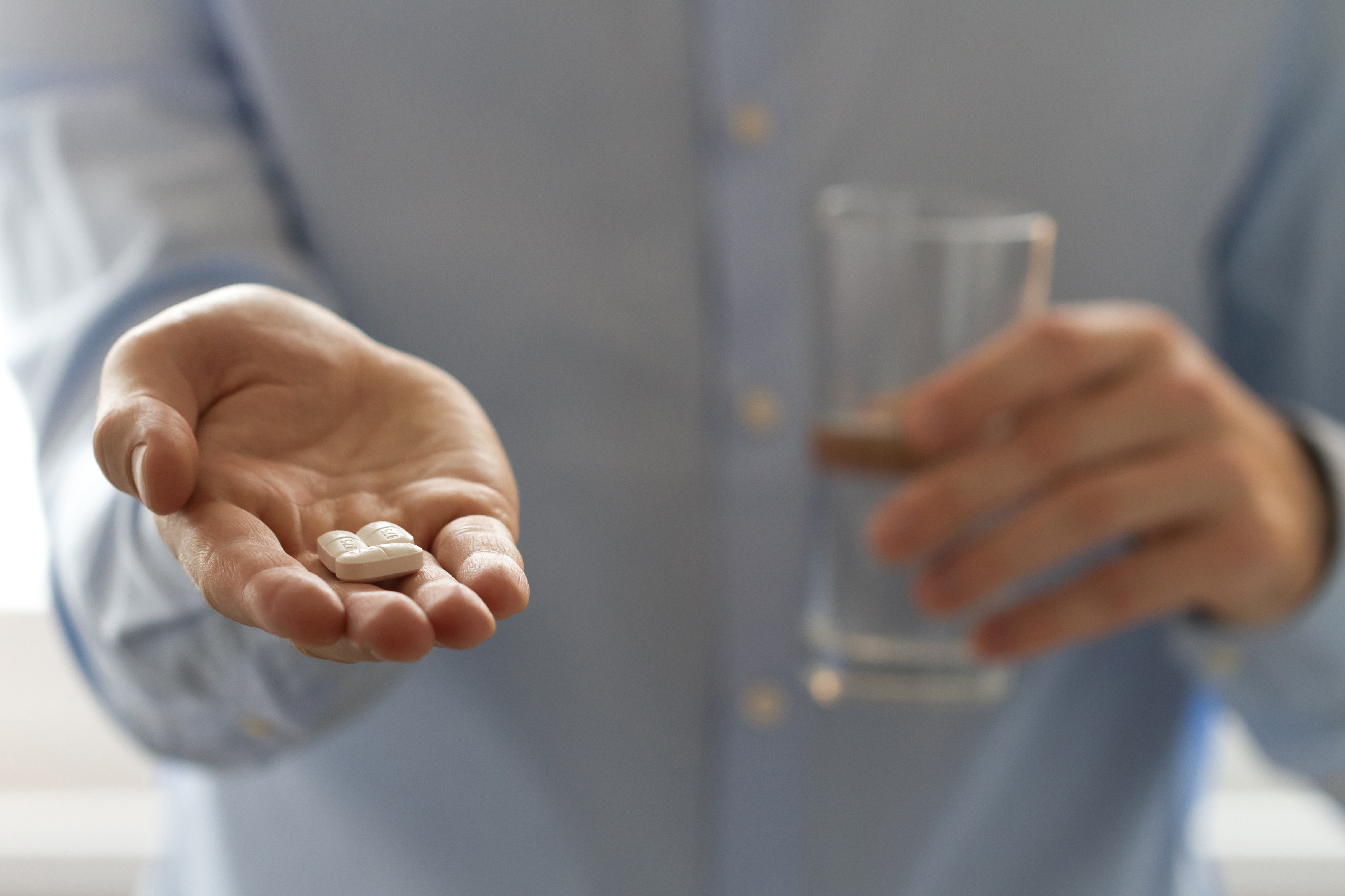 Man holding pills in one hand and glass