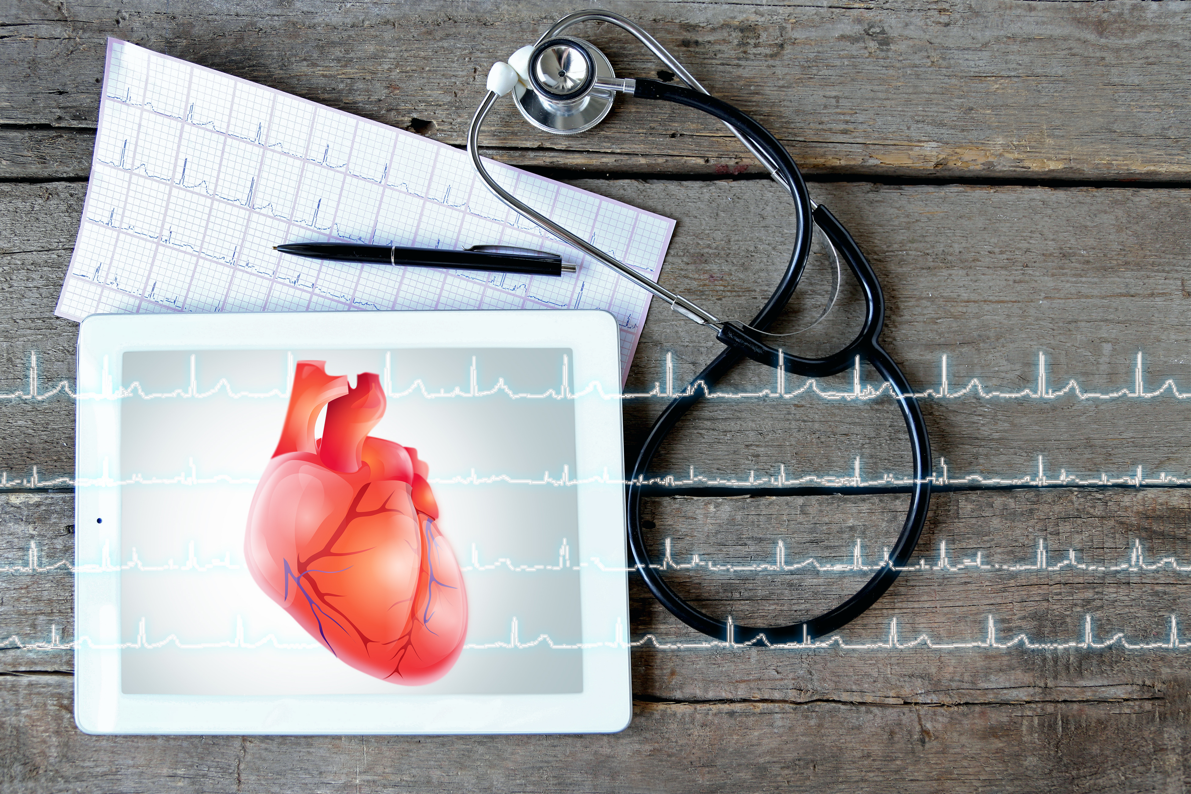 Tablet with stethoscope on wooden background. Heart on screen. Medicine and modern technology concept.