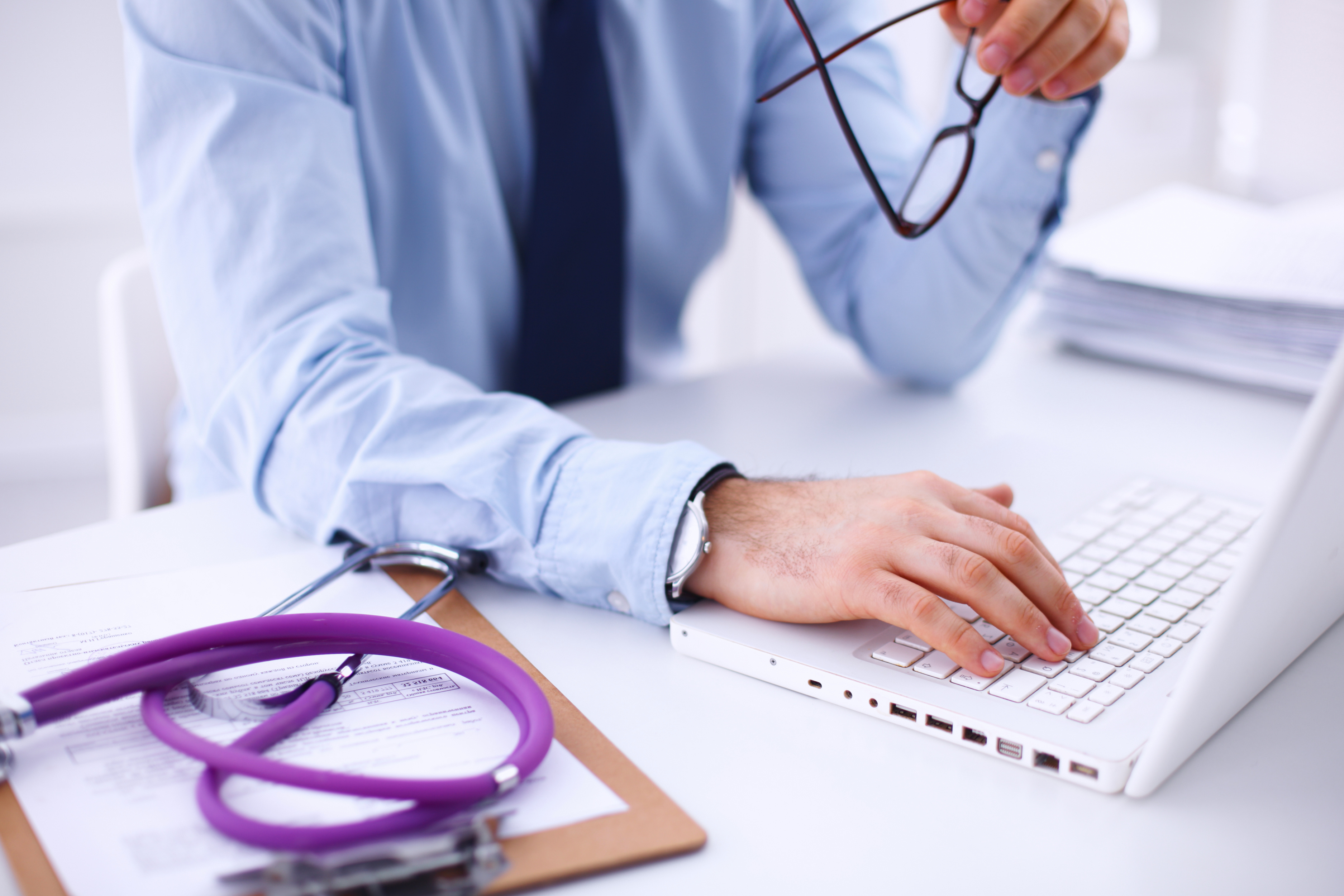 Male doctor using a laptop, sitting at his desk .