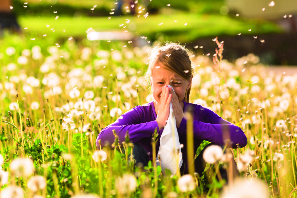 Girl sitting in a meadow with dandelions and has hay fever or allergy