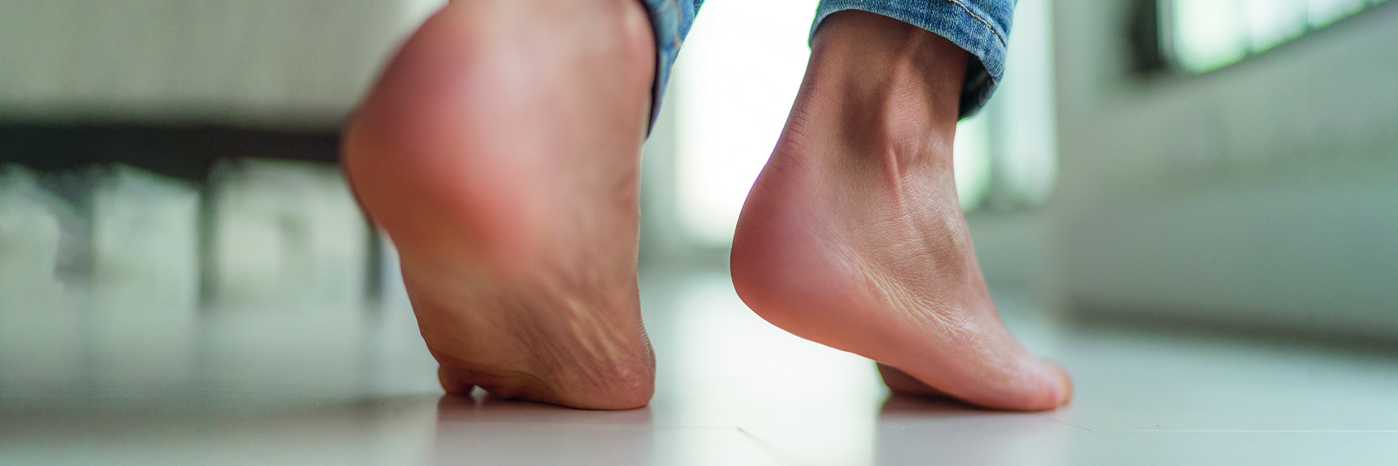 Barefoot feet walking on heated floors at home - Comfort lifestyle healthy foot care for cracked skin heels woman legs banner panorama.