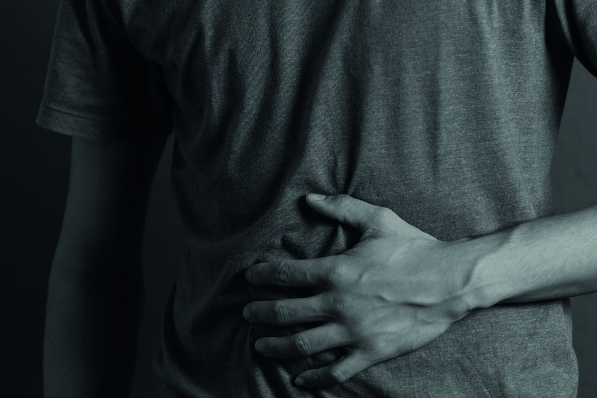 Close up of young man suffering from stomach ache standing
