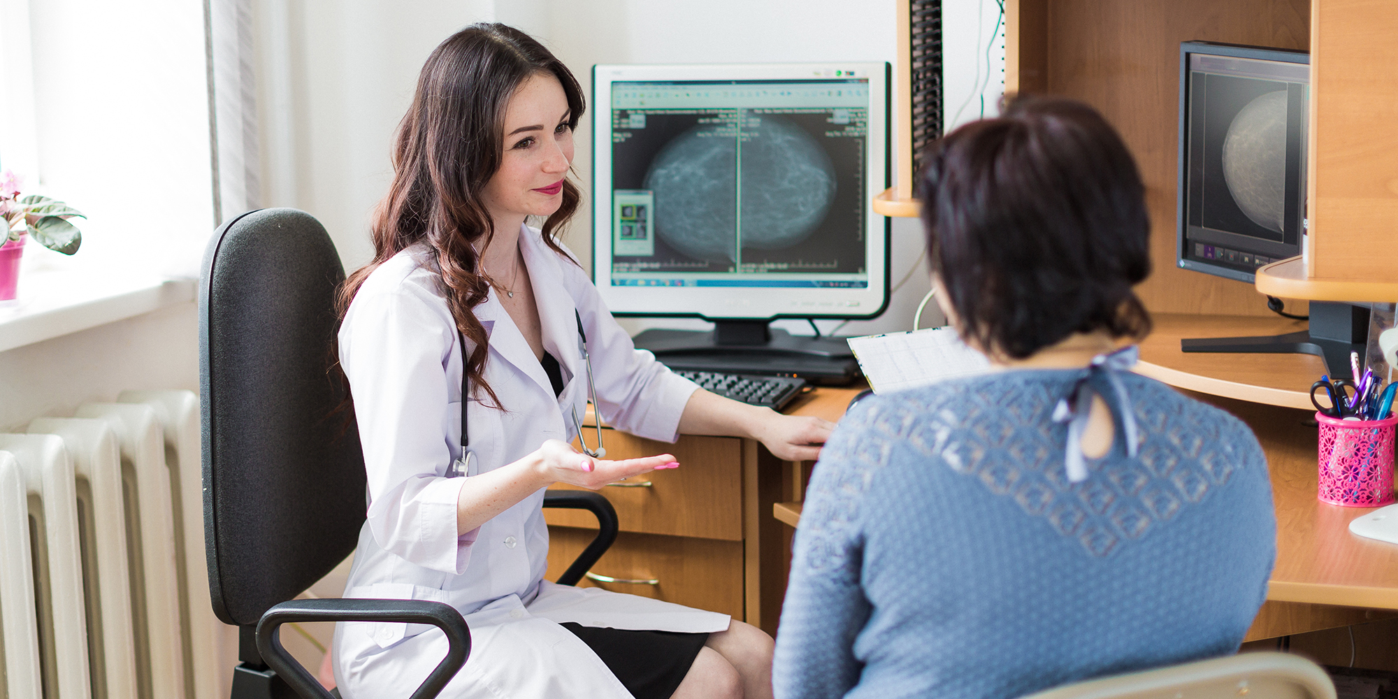 The young happy breast specialist talking with the patient in her office