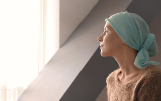 Young woman with cancer in headscarf indoors