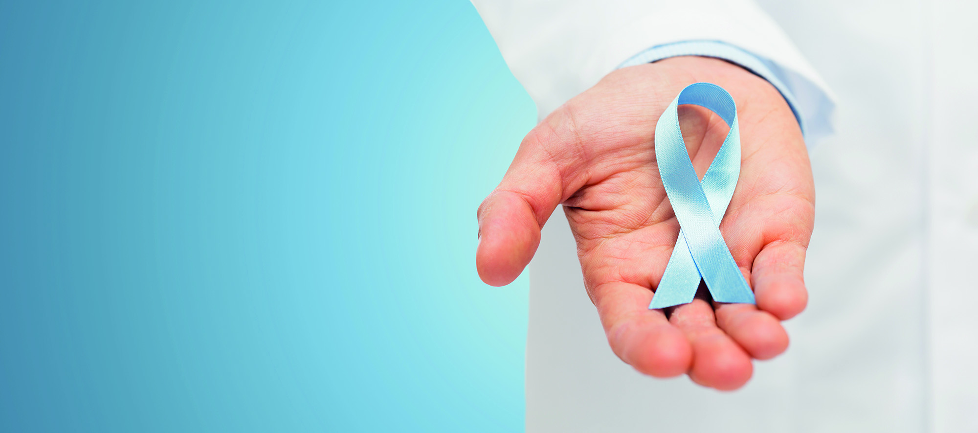healthcare, profession, people and medicine concept - close up of male doctor hand holding sky blue prostate cancer awareness ribbon over blue background