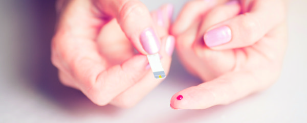 medicine, diabetes, glycemia, health care and people concept - close up of female finger with blood drop and test stripe