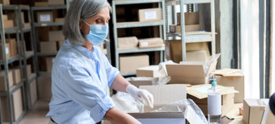 Mature female volunteer warehouse worker wearing face mask working in shipping delivery charitable stock organization packing medical donations box. Covid 19 coronavirus donating and volunteering.